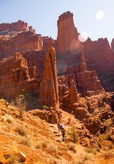 Verticaal schot van mensen die de heuvel dichtbij een woestijnklip overdag lopen