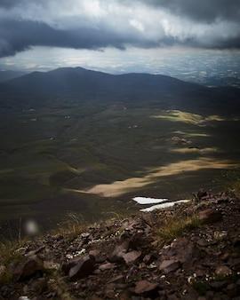 Verticaal schot van met gras begroeide heuvels onder een bewolkte hemel
