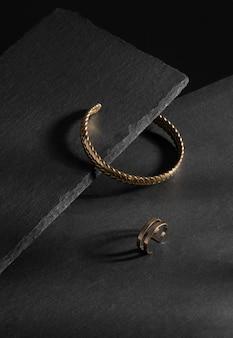 Verticaal schot van moderne design gouden armband en ring op zwarte stenen dienbladen met kopieerruimte