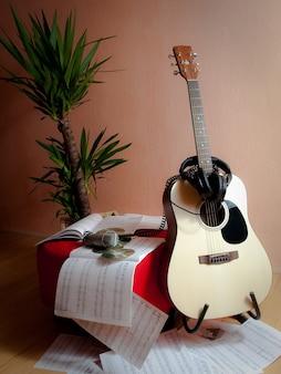 Verticaal schot van muzieknoten naast een gitaar, hoofdtelefoons en een installatie