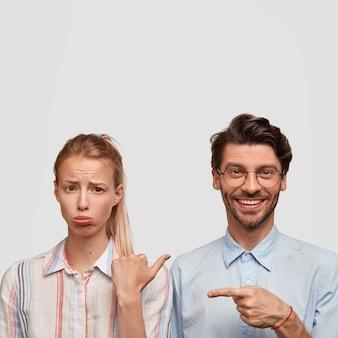 Verticaal schot van ontevreden blonde vrouw portemonnees onderlip, beledigd door kerel. positieve ongeschoren hipster met aangename glimlach, wijst naar vriendin, geïsoleerd over witte muur, vrije ruimte