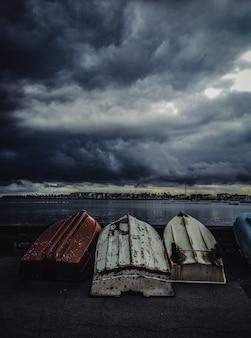 Verticaal schot van oude vissersboten ondersteboven gekeerd onder de sombere lucht