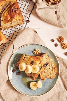Verticaal schot van plakjes heerlijk bananenbrood met chocoladestukjes en walnoot op een bord
