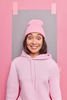 Verticaal schot van positief goed uitziend aziatisch meisje lacht gelukkig hoort uitstekend nieuws draagt vrijetijdskleding heeft gefascineerde expressie poses tegen blanco kopieerruimte checkt iets geweldigs