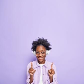 Verticaal schot van positief millennial meisje met donkere huid en krullend haar draagt grote transparante bril luistert muziek demonstreert lege kopieerruimte gekleed in modieuze kleding geïsoleerd op paarse muur