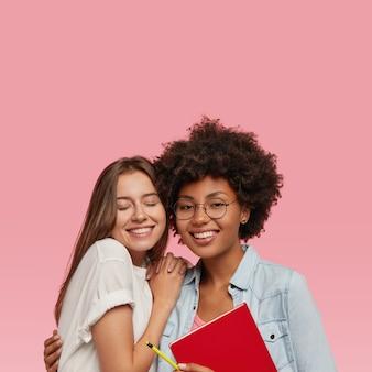 Verticaal schot van positieve gemengde ras jonge vrouwen of zusters hebben samen vreugde
