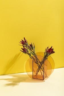 Verticaal schot van prachtige rode billbergia-bloemen in een glazen vaas tegen een gele muur