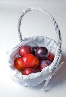 Verticaal schot van pruimen in een klein mandje geïsoleerd op grijs