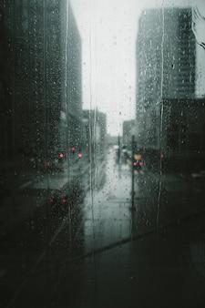 Verticaal schot van regendruppels die een glasvenster naar beneden gieten