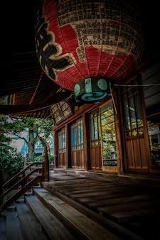 Verticaal schot van rode lantaarn over de treden dichtbij het houten huis in japanse stijl