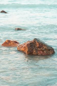 Verticaal schot van rotsen op het strand met kalmerende golven van de oceaan