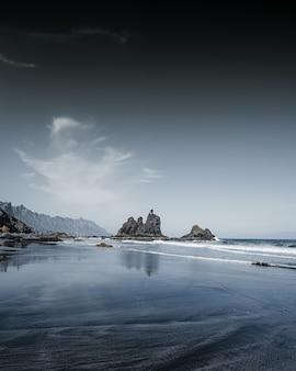 Verticaal schot van rotsformaties in het water van de zee