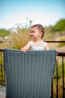 Verticaal schot van schattig babymeisje met witte jurk staande op stro stoel en lachen