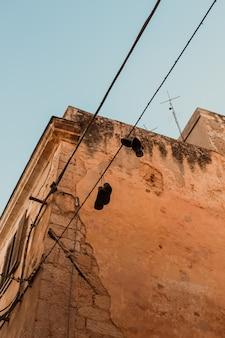 Verticaal schot van schoenen die van een elektrische kabel dichtbij een gebouw onder een blauwe hemel inleveren