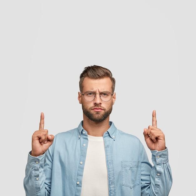 Verticaal schot van serieuze ongeschoren man houdt beide wijsvingers omhoog, toont vrije ruimte boven het hoofd