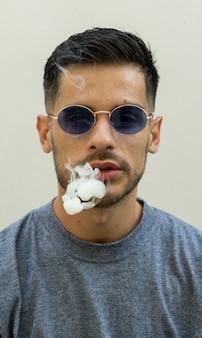 Verticaal schot van sigarettenrook die uit een jonge blanke man met een zonnebril komt