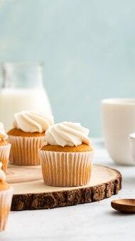 Verticaal schot van smakelijke cupcakes met room bovenop op een houten plakje