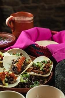 Verticaal schot van smakelijke tortilla's met vlees en tomatensaus op ingrediënten
