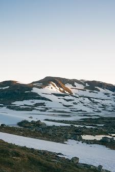 Verticaal schot van sneeuw en stenen op een heuvel