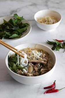 Verticaal schot van soep pho bo met stokken daarin, vietnamees eten, vietnamese keuken