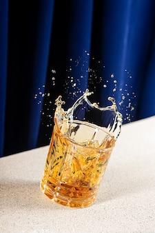 Verticaal schot van spetterende whisky in een glas met een blauw gordijn op de achtergrond