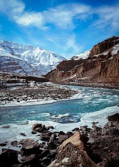 Verticaal schot van spiti-vallei in de winter met bevroren rivier en sneeuwpiekbergen