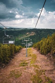 Verticaal schot van stoeltjesliften omgeven door heuvels bedekt met groen onder een bewolkte hemel
