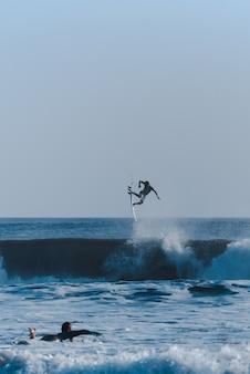 Verticaal schot van surfers die trucs doen in de oceaan die de golven overnemen