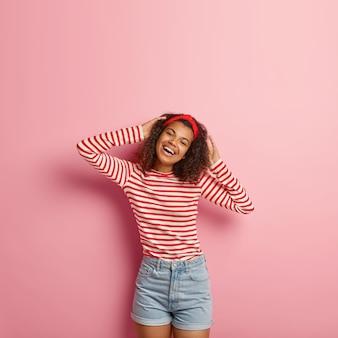 Verticaal schot van tienermeisje met krullend haar poseren in gestreepte rode trui