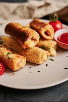 Verticaal schot van toostbroodjes met ham en kaas en tomaten en ketchup op een witte plaat