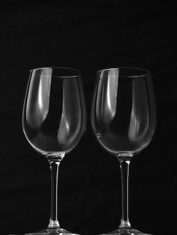 Verticaal schot van twee lege wijnglazen op zwarte achtergrond