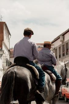 Verticaal schot van twee mannen die paarden door de stad berijden