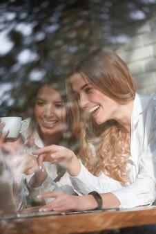 Verticaal schot van twee mooie gelukkige jonge vrouwen die laptp samen gebruiken bij de plaatselijke coffeeshop vriendschap vrienden communicatie zusters binding vrije tijd saamhorigheid emoties positiviteit internet.