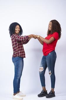 Verticaal schot van twee mooie jonge afrikaanse vrouwen die met de vuist stoten