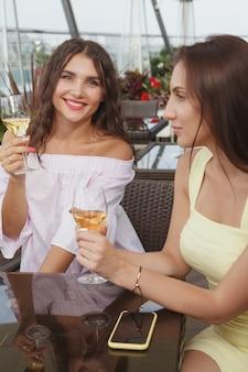 Verticaal schot van twee mooie vrouwen die samen bij bar op het dak drinken