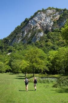 Verticaal schot van twee vrouwenwandelaars die in de groene aard van cerdon, ain, in oostelijk frankrijk wandelen
