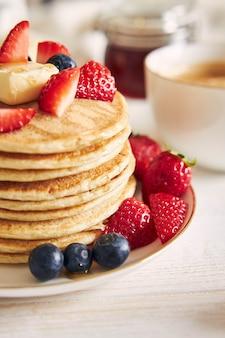 Verticaal schot van veganistische pannenkoeken met fruit op witte plaat