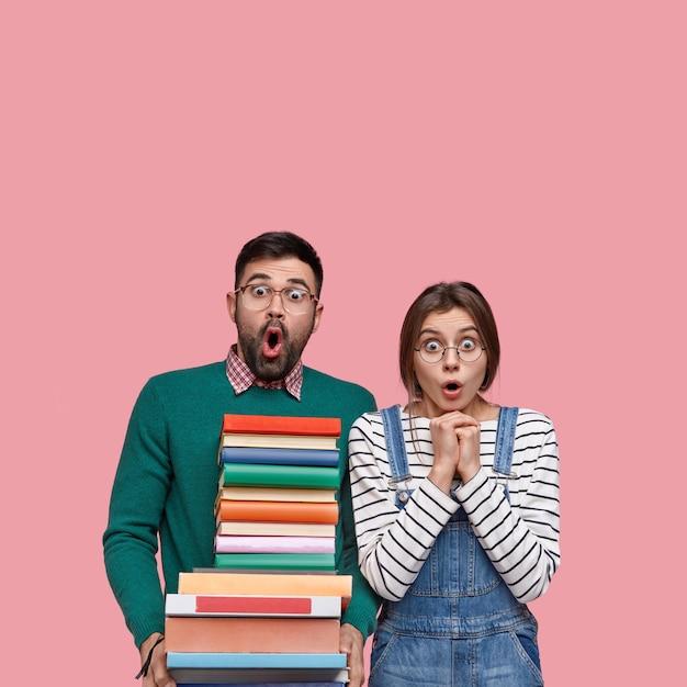 Verticaal schot van verbaasde hipster en vriendin hebben deadline-taak, open mond van verbazing, sta dicht, lees wetenschappelijke literatuur