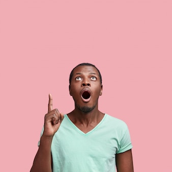 Verticaal schot van verbaasde jonge afro-amerikaanse man met wijd geopende mond, heeft onverwachte uitdrukking, gekleed in casual t-shirt, geïsoleerd over roze
