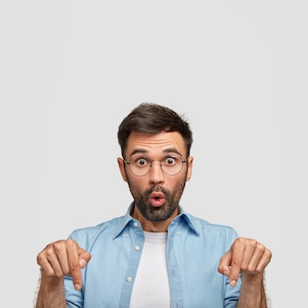 Verticaal schot van verbijsterde blanke man wijst naar beneden, toont iets, gekleed in een casual blauw shirt, geïsoleerd op een witte muur