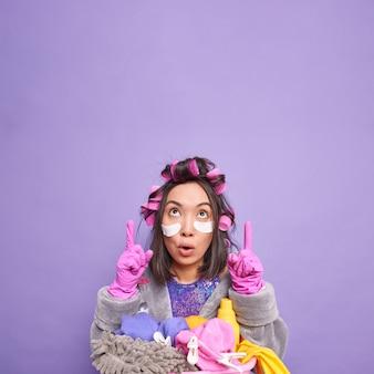 Verticaal schot van verraste aziatische vrouw huisvrouw poseert in de buurt van stapel wasgoed bezig huishoudster wijst hierboven op kopieerruimte past haarrollers toe schoonheidspatches adverteert product voor reiniging