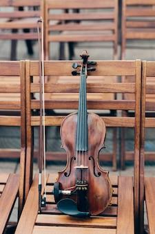 Verticaal schot van viool met boog op houten stoel.