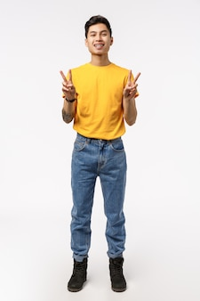 Verticaal schot van volledige lengte charmante chinese man in geel t-shirt, spijkerbroek, vredesteken weergegeven en glimlachend gelukkig, positiviteit uitdrukken, plezier maken, vermaakt en blij staan, witte muur