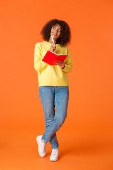 Verticaal schot van volledige lengte dromerig en romantisch schattig meisje dat een schema maakt, aantekeningen maakt of een takenlijst maakt, iets afbeeldt als schrijven in een rood schattig notitieboekje, kin aanraken met pen en doordacht opzoekt.