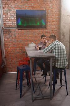 Verticaal schot van volledige lengte van mannen die bier drinken in de pub