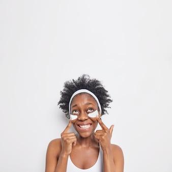 Verticaal schot van vrolijke krullende afro-amerikaanse vrouw wijst naar onder de ooglapjes en glimlacht breed broad