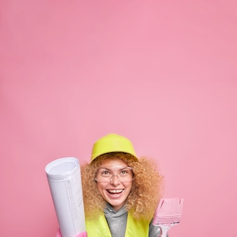 Verticaal schot van vrolijke krullende vrouw draagt veiligheidshelm transparante bril houdt blauwdruk vast en verfborstel komt op bouwplaats