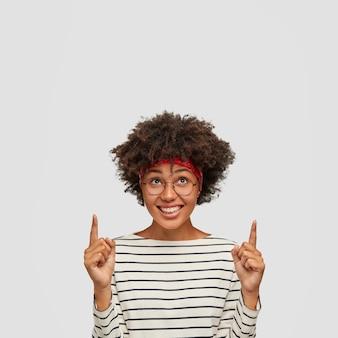 Verticaal schot van vrolijke vrouw met afro-kapsel