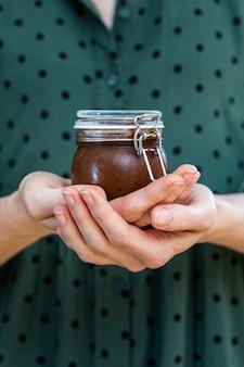 Verticaal schot van vrouwelijke handen met een zelfgemaakte veganistische rauwe pruimenjam in een glazen pot