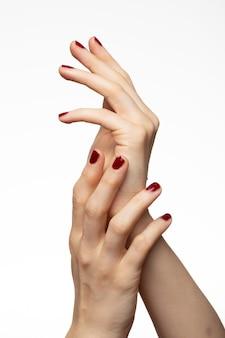 Verticaal schot van vrouwelijke handen met rode nagellak